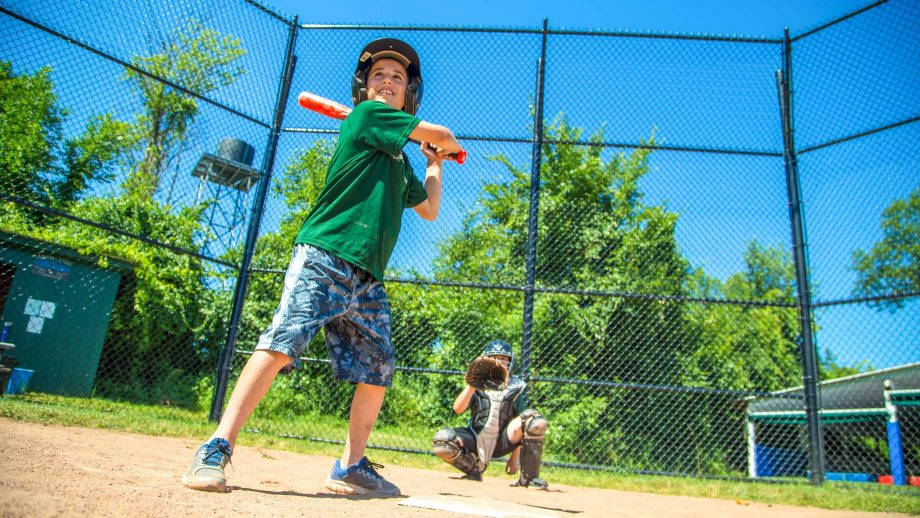 Boy swing baseball bat during summer camp game