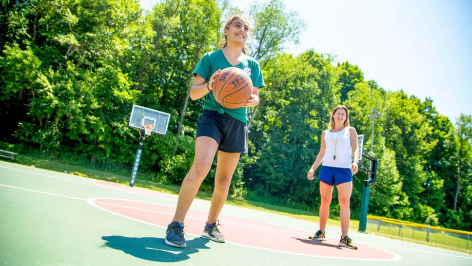 Girl holds basketball during summer camp game
