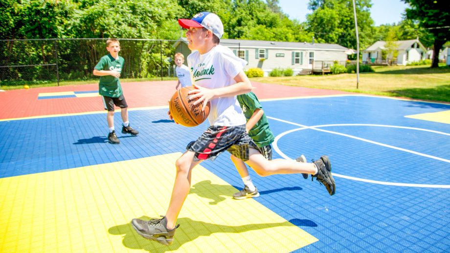 Boy runs with basketball during summer camp game