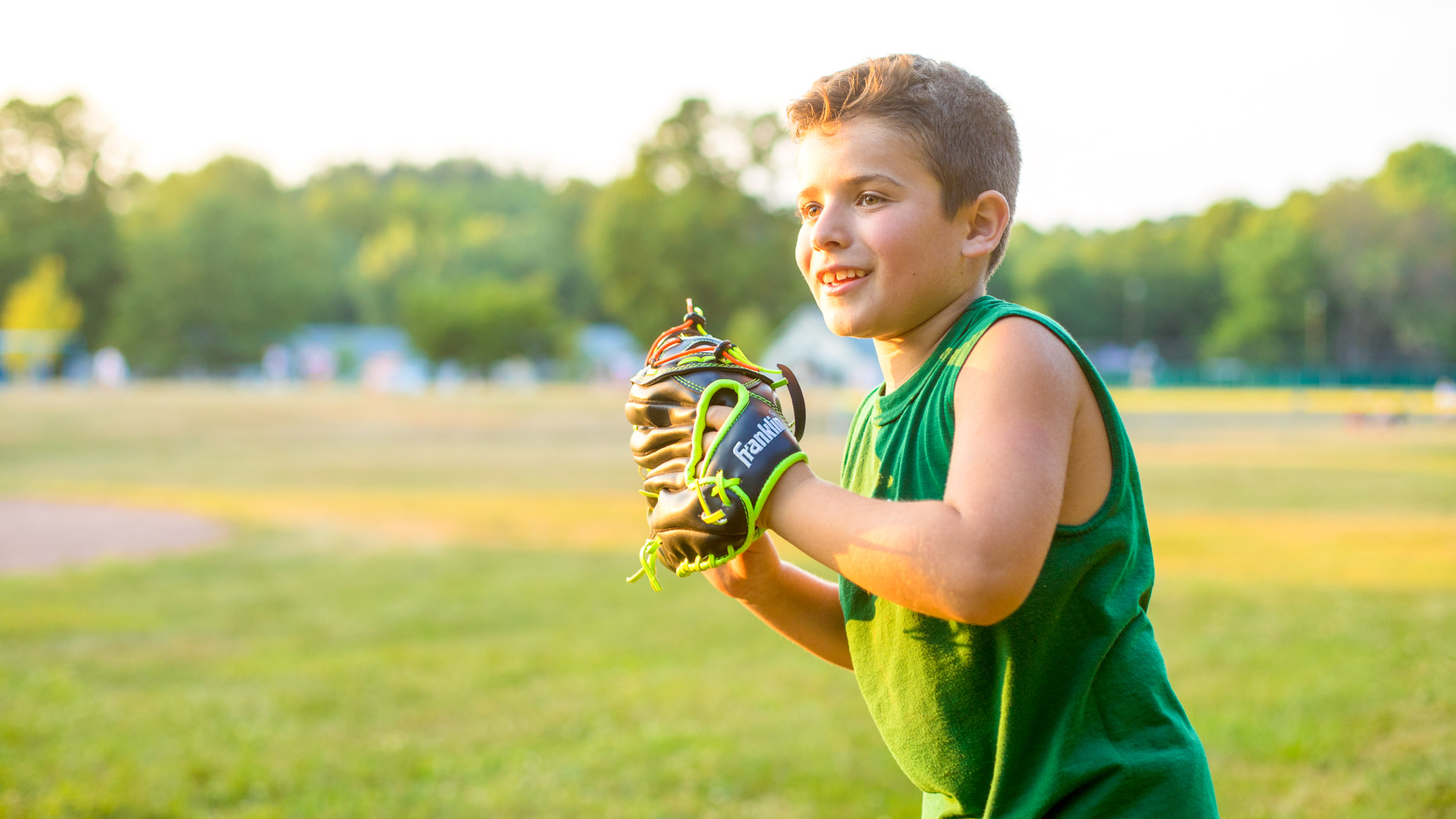 Boy pitches baseball during summer camp game