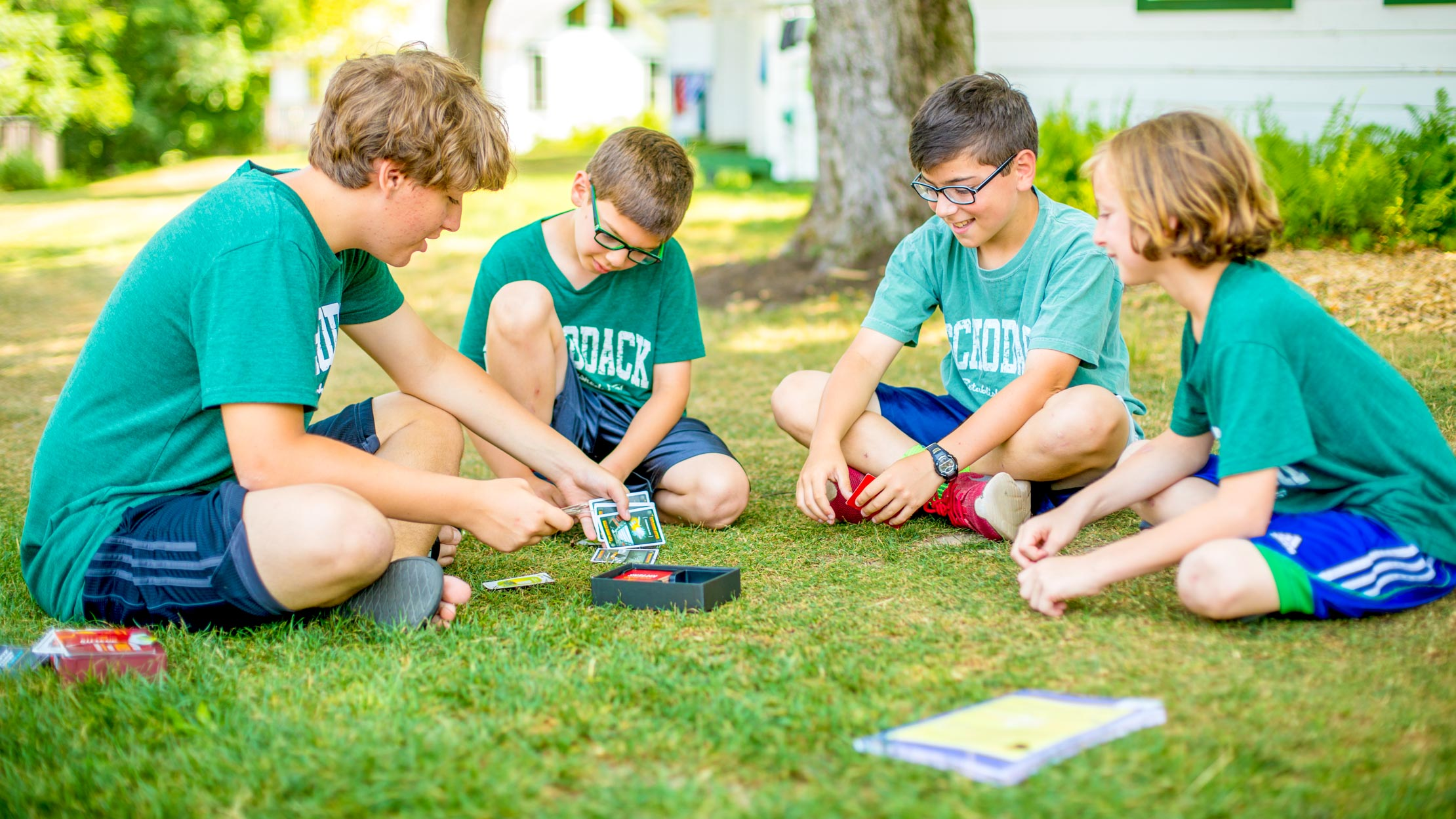 Boys playing cards on the grass at summer camp