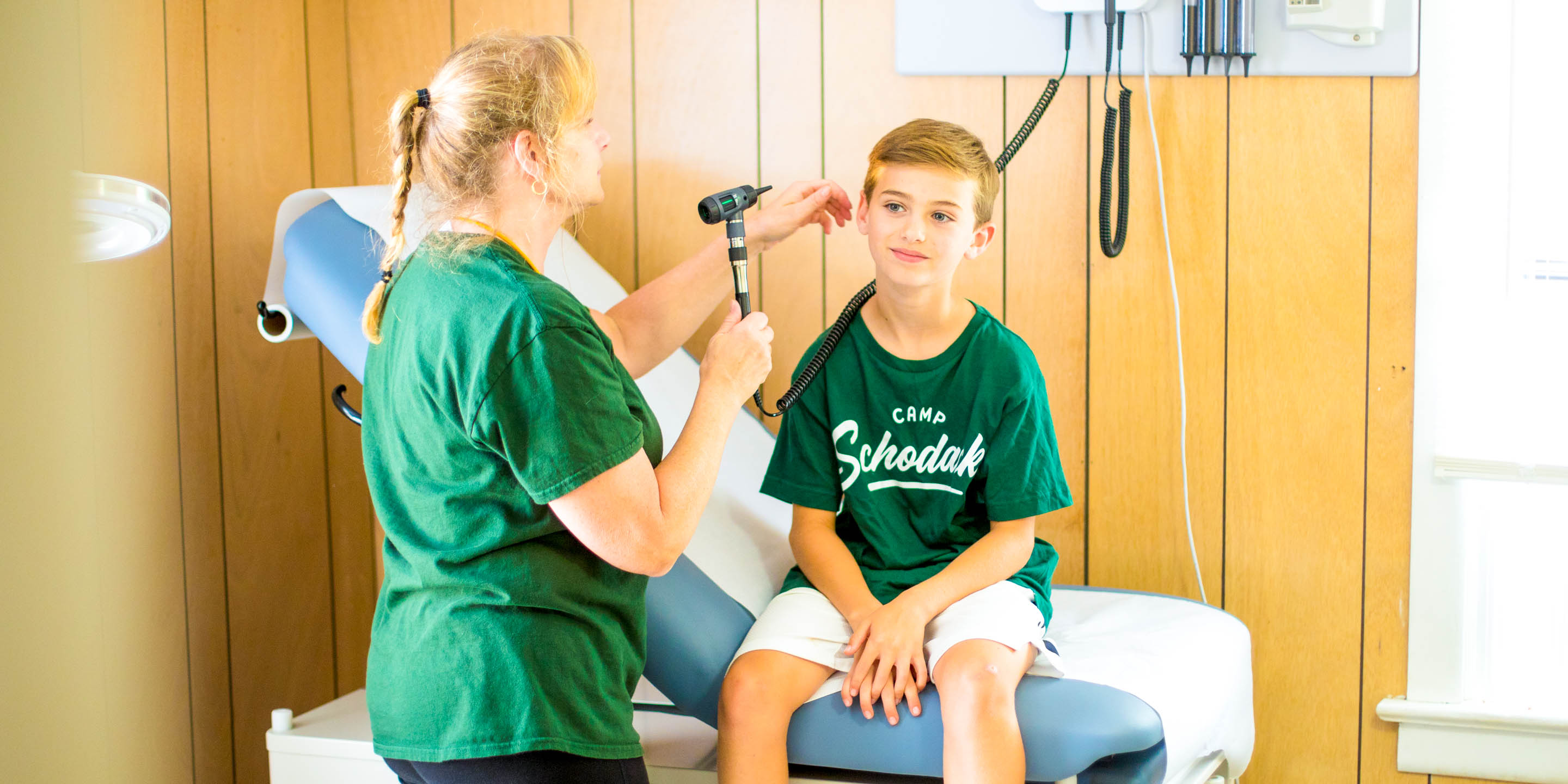 Summer camp nurse performs health check-up on camper