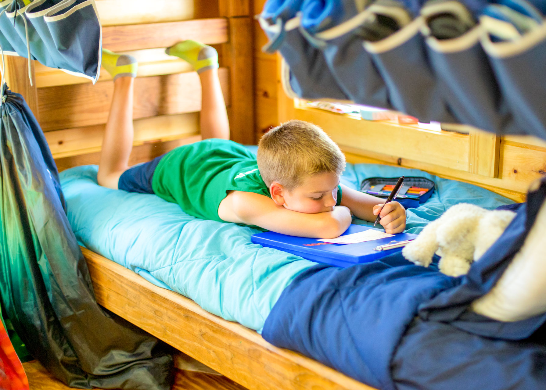 Young boy lies on camp bunk to write