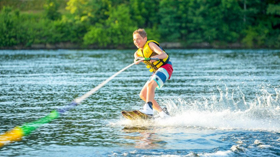 Boy wakeboards at summer camp