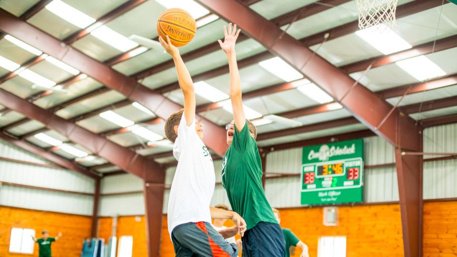 Camper jumps to block shot on hoop during basketball