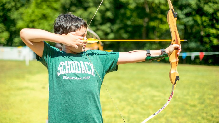 Boy draws bow during summer camp archery