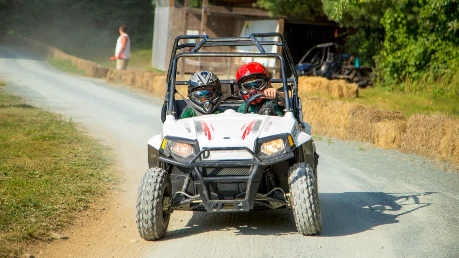 Campers drive go-kart around summer camp track