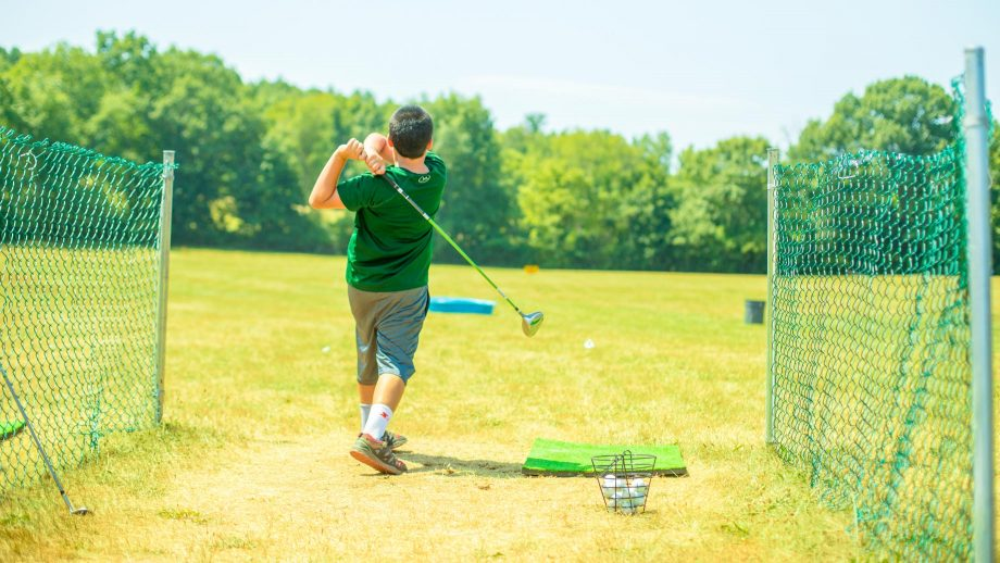 Boy using Camp Schodack golf driving range