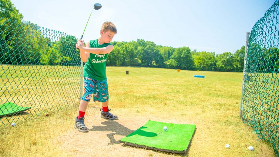 Boy swing golf club at summer camp driving range