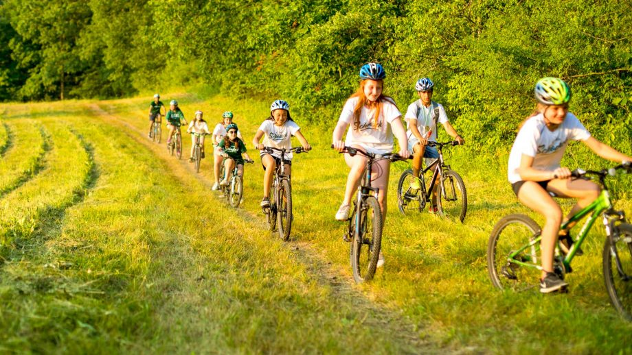Group of girls mountain bikes through field
