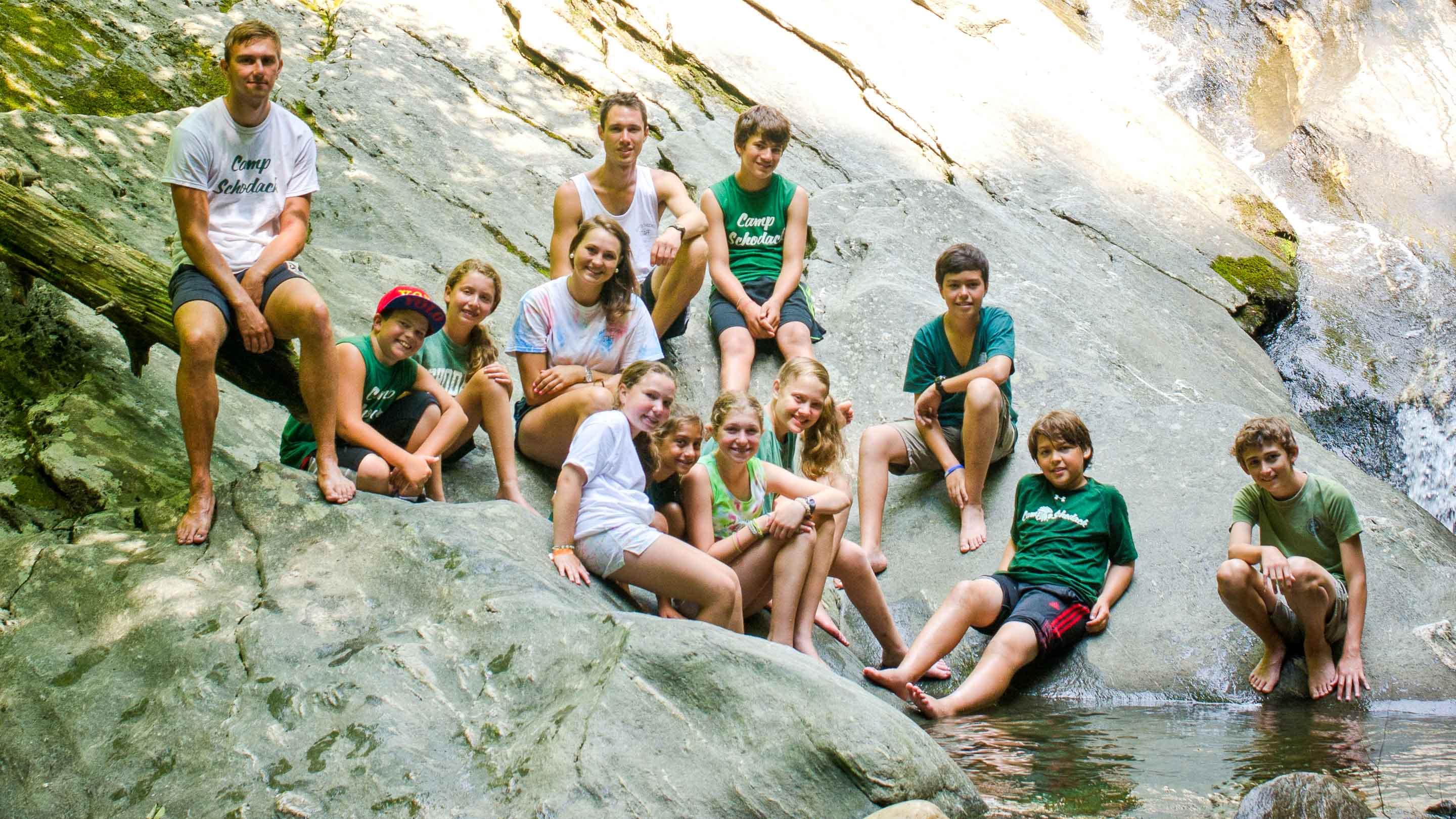 Group of campers sits next to rock pool
