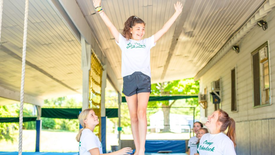 Smiling girl raises arms on balance beam