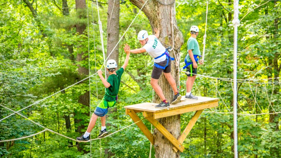 Camper and staff member high five on high ropes course