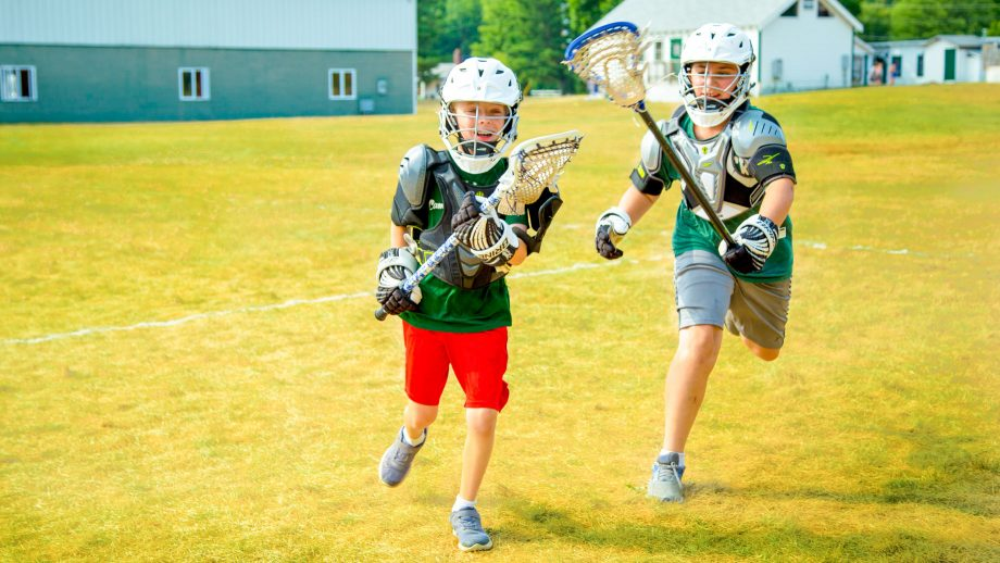 Boys run during summer camp lacrosse game