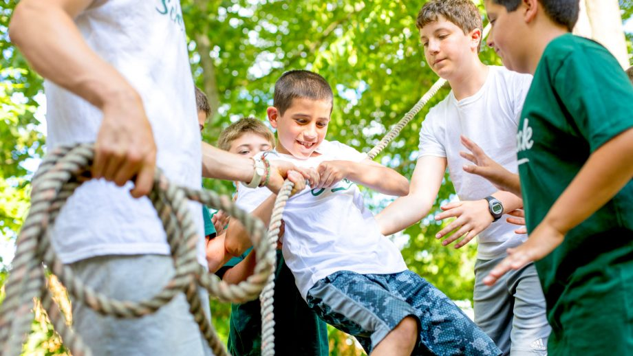 Group of campers support boy on low ropes course