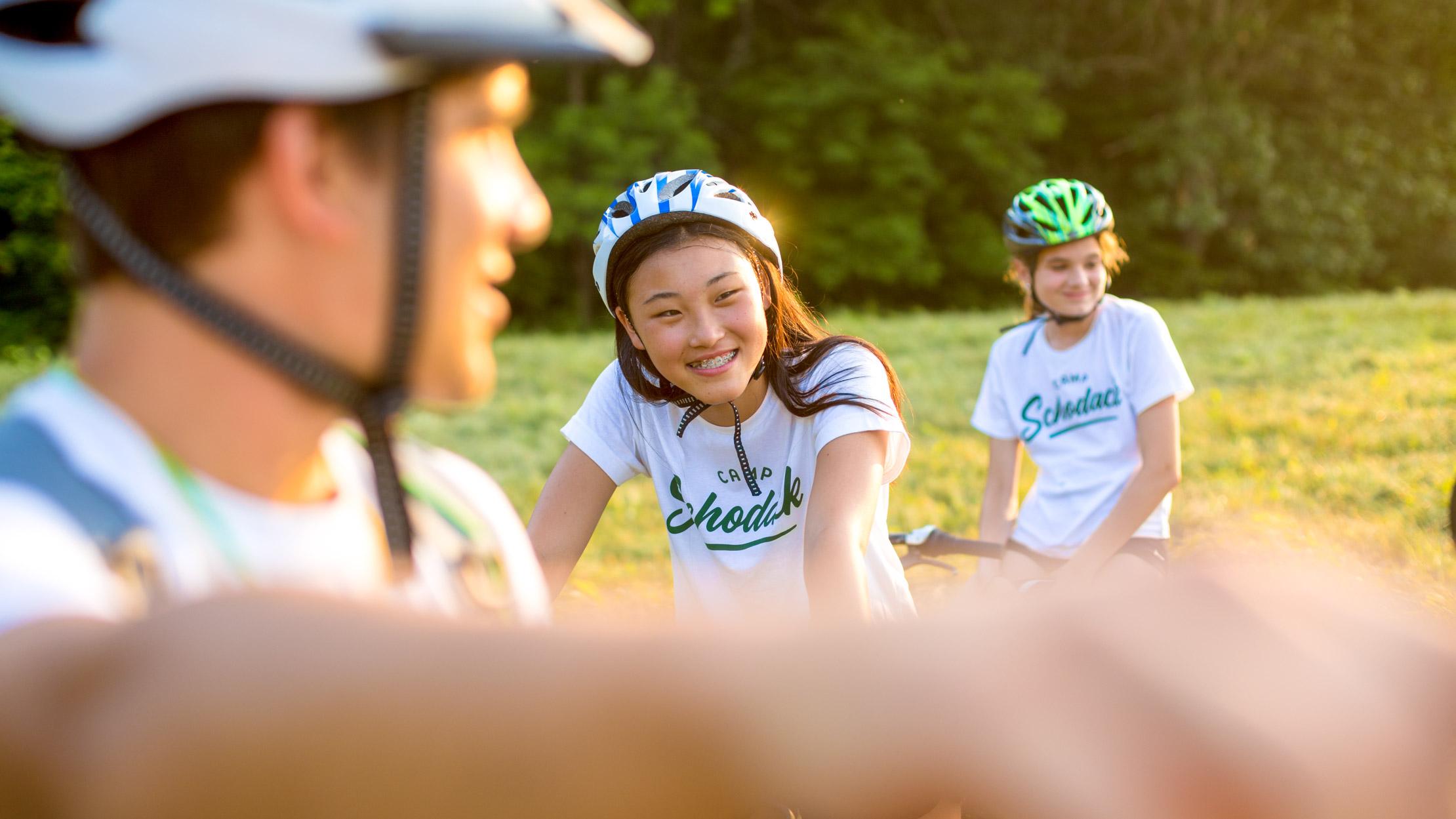 Girl smiles while mountain biking at summer camp
