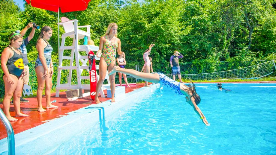 Girl dives into pool at summer camp