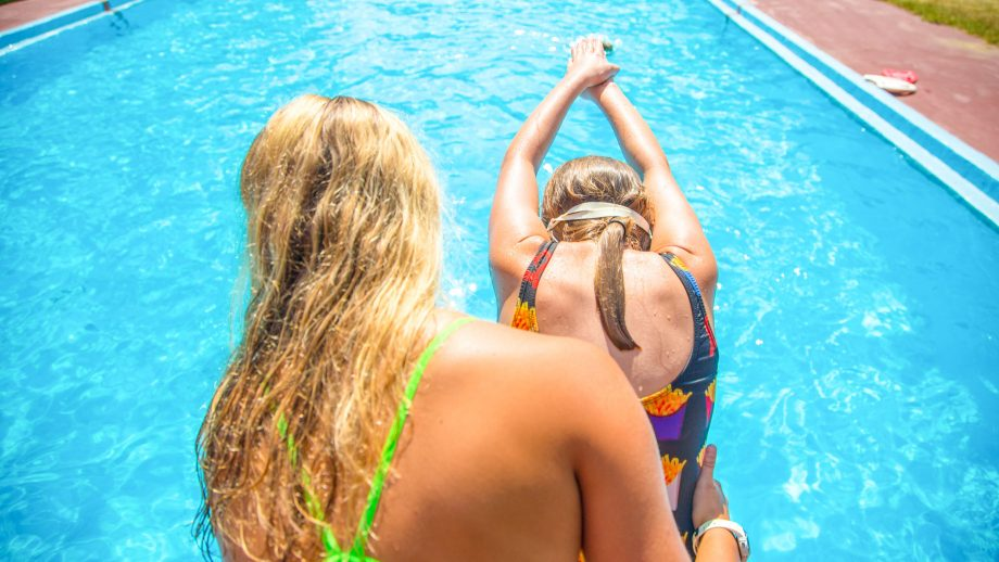 Swim instructor helps camper dive into pool