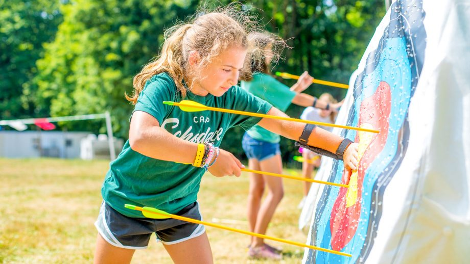 Girl retrieves arrows during summer camp archery