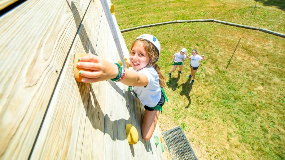 Girl reaches for handhold on rock climbing wall