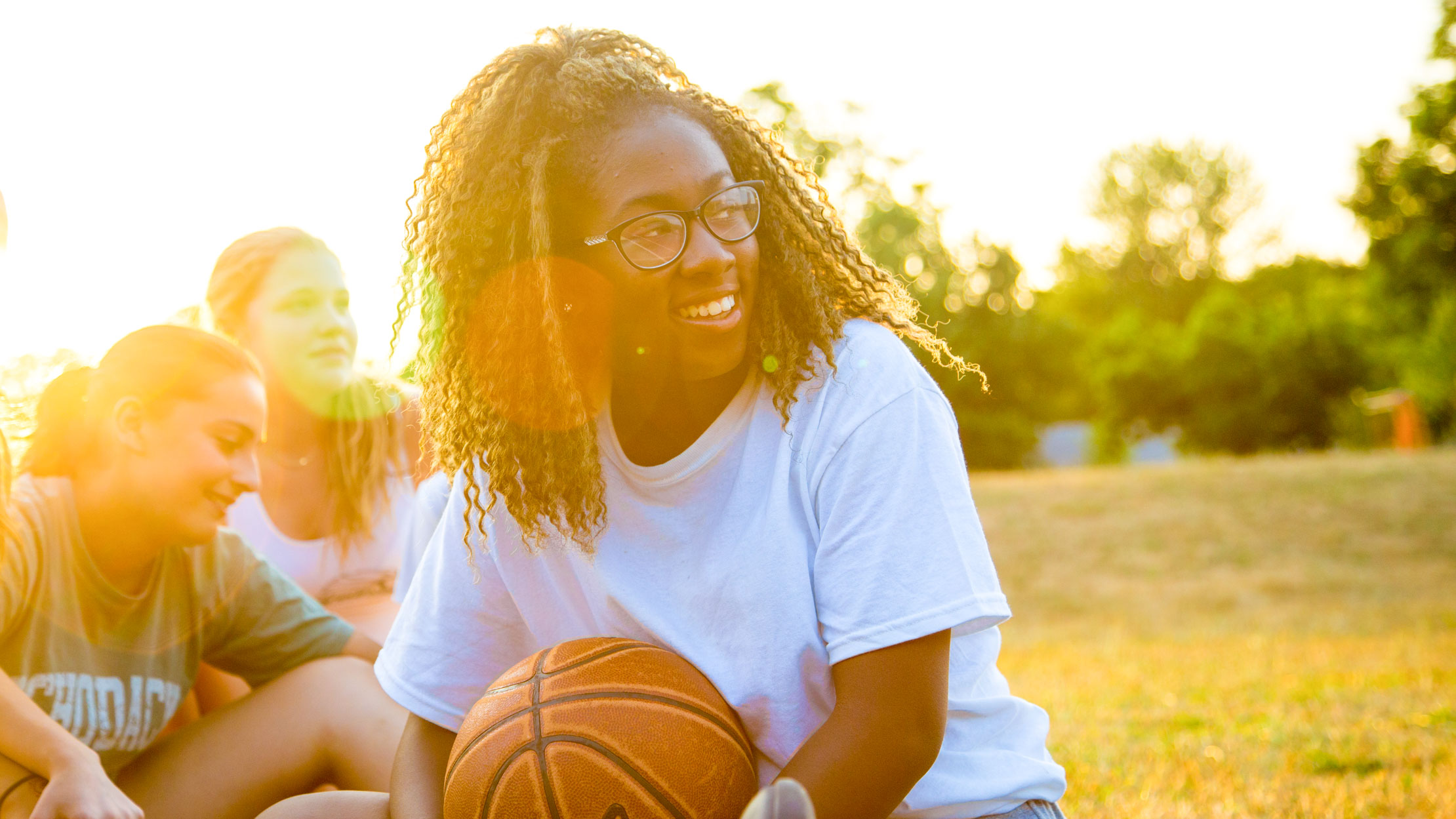 Smiling girl holds basketball at sunset