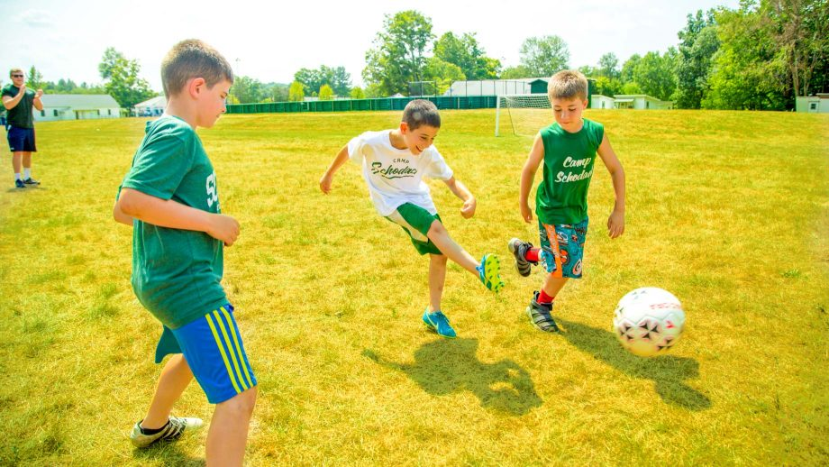 Boy kicks soccer ball during summer camp game