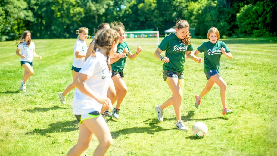 Girls play soccer at summer camp