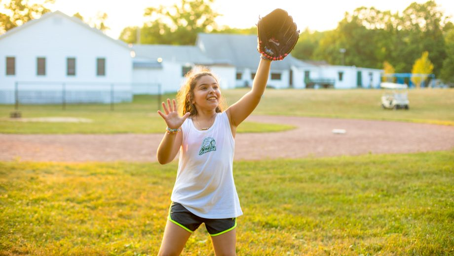 Girl prepares to catch softball during summer camp game
