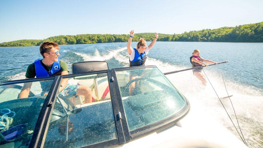 Staff member on speedboat cheers for waterskiing camper