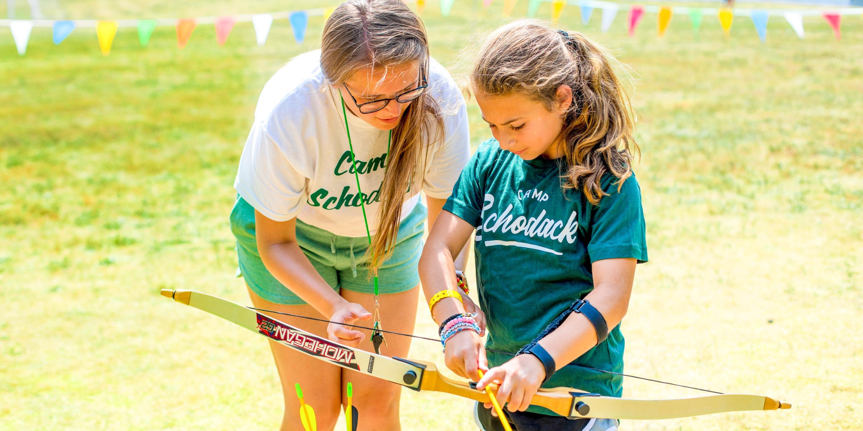 Staff member helps camper nock arrow for archery