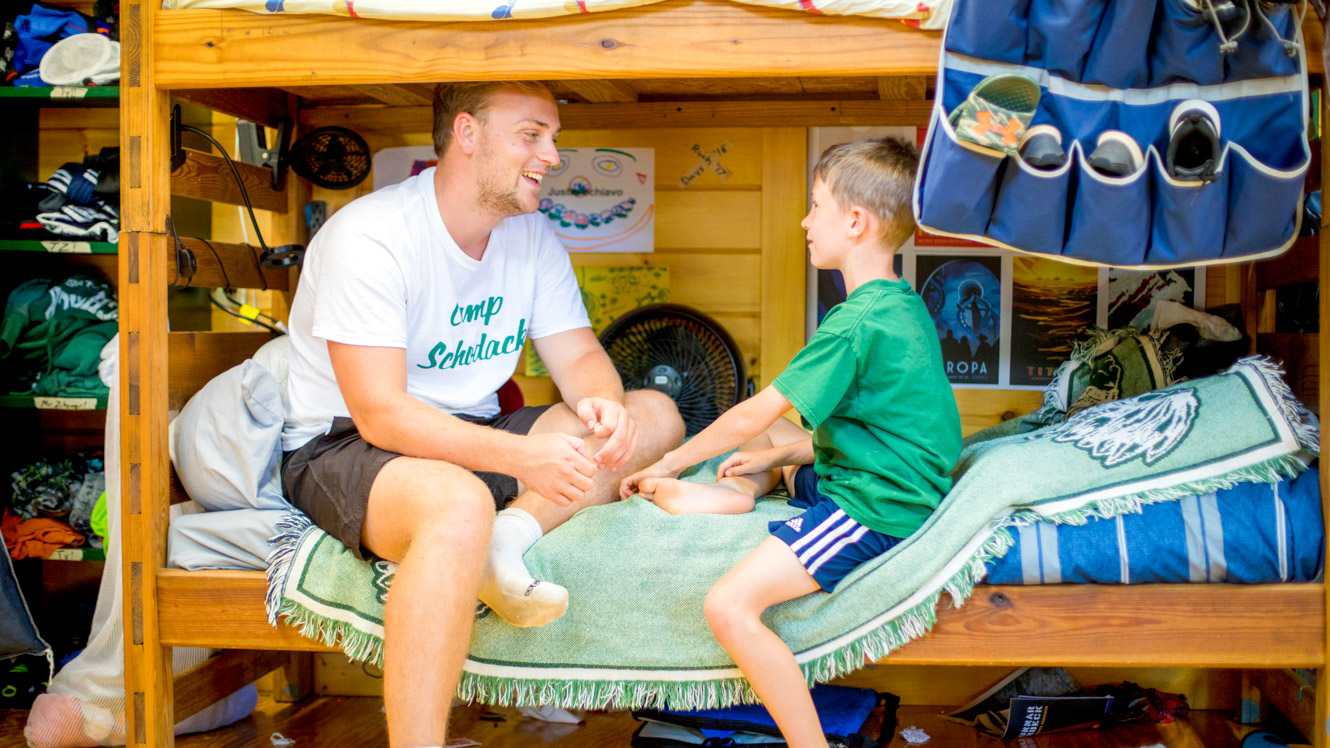 Counselor and camper sit on bunk to chat