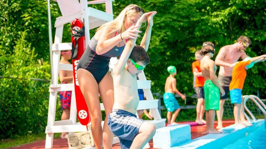 Lifeguard helps camper practice dive form