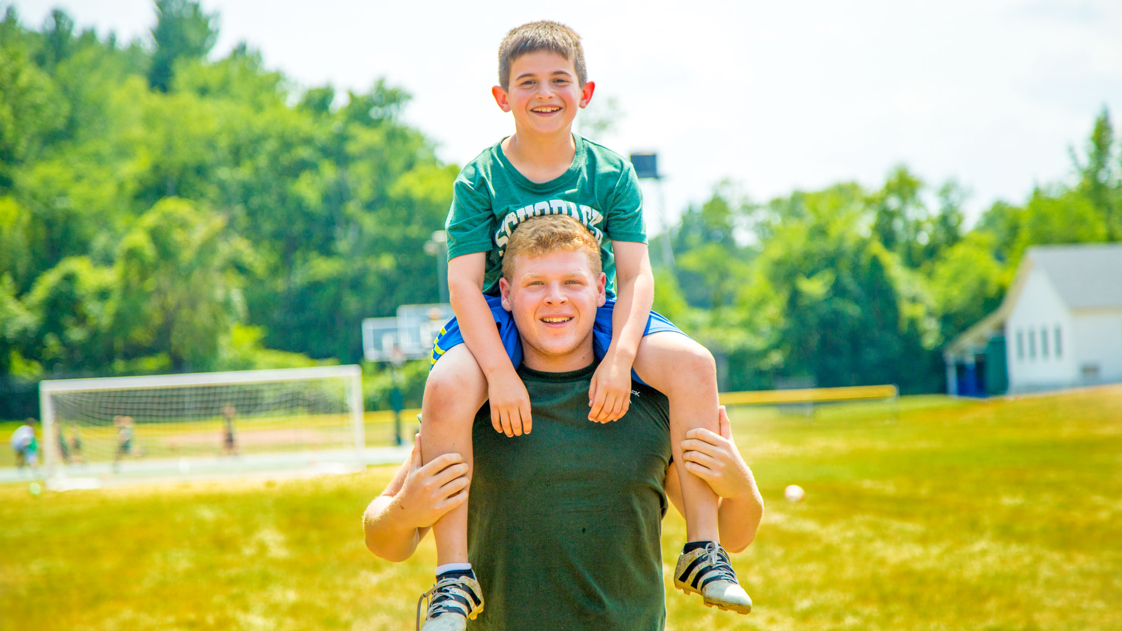 Counselor carries camper on his shoulders