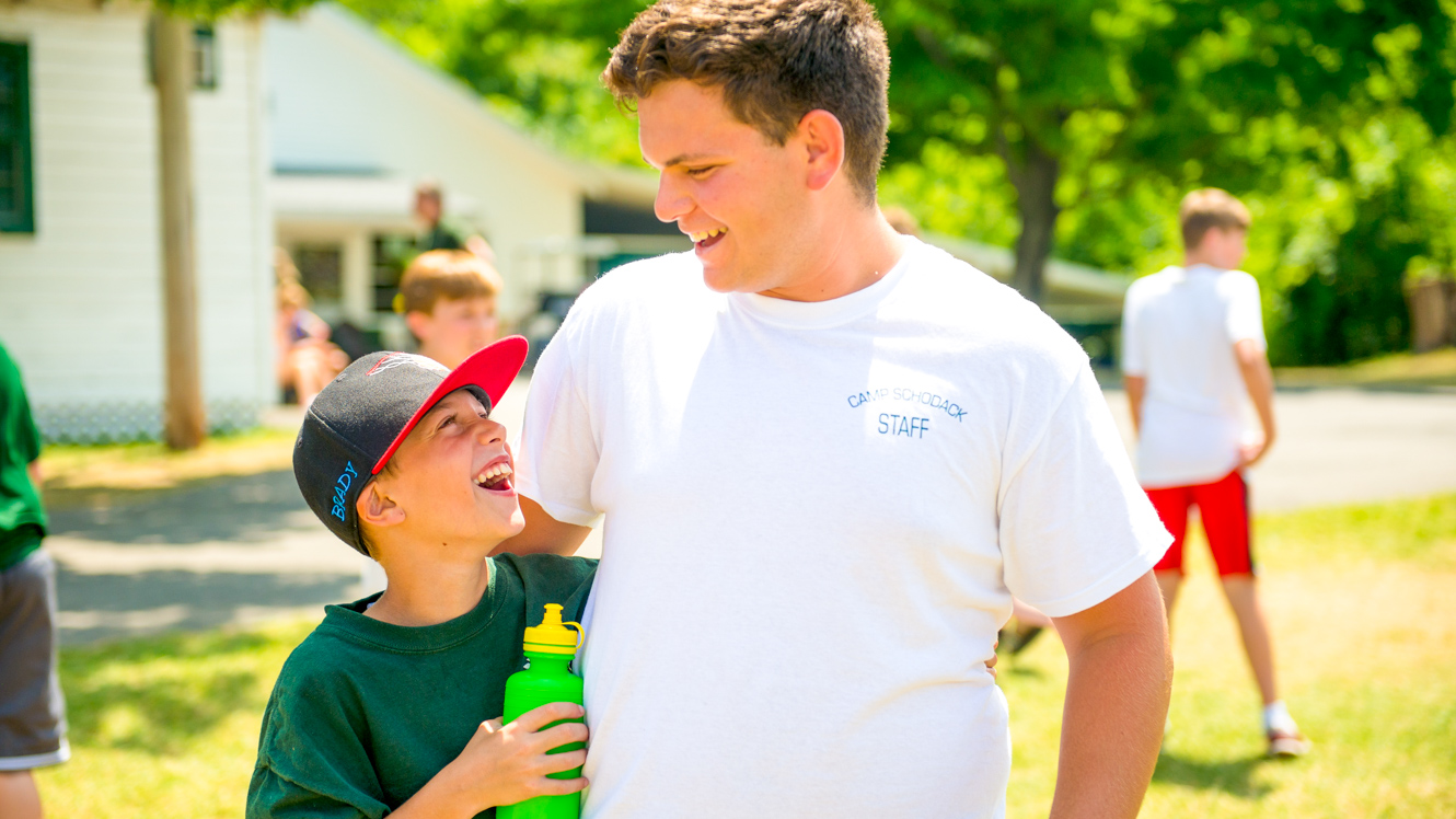 Boy smiles up at summer camp counselor