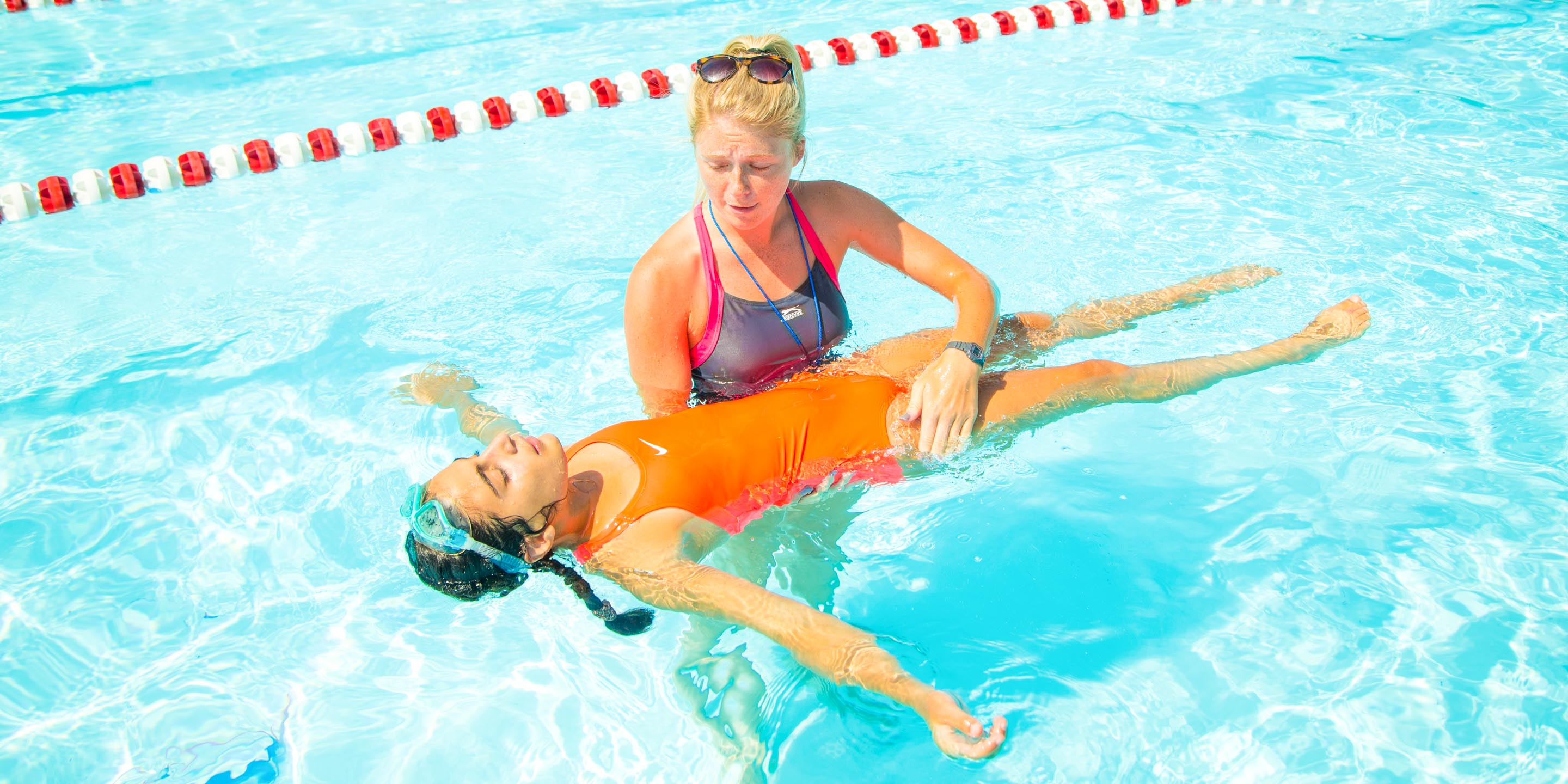 Activity counselor helps camper float on back in water