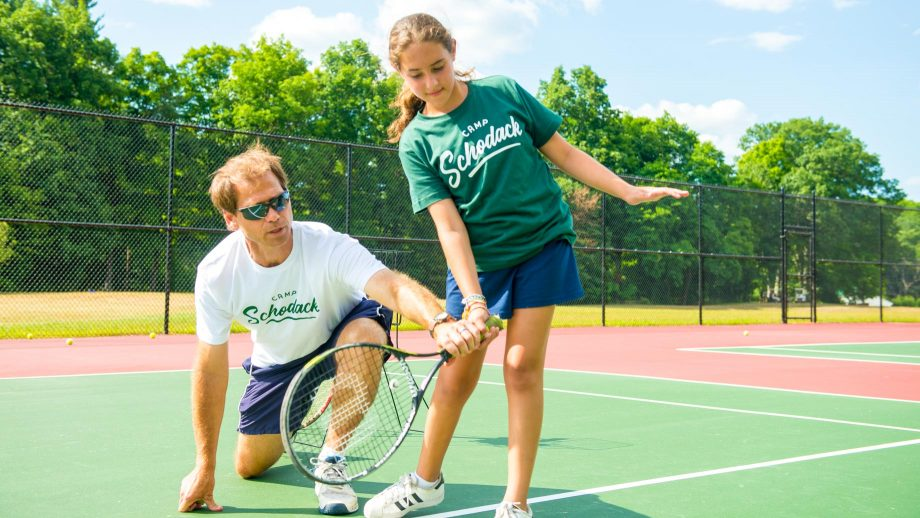 Staff member helps camper with tennis swing