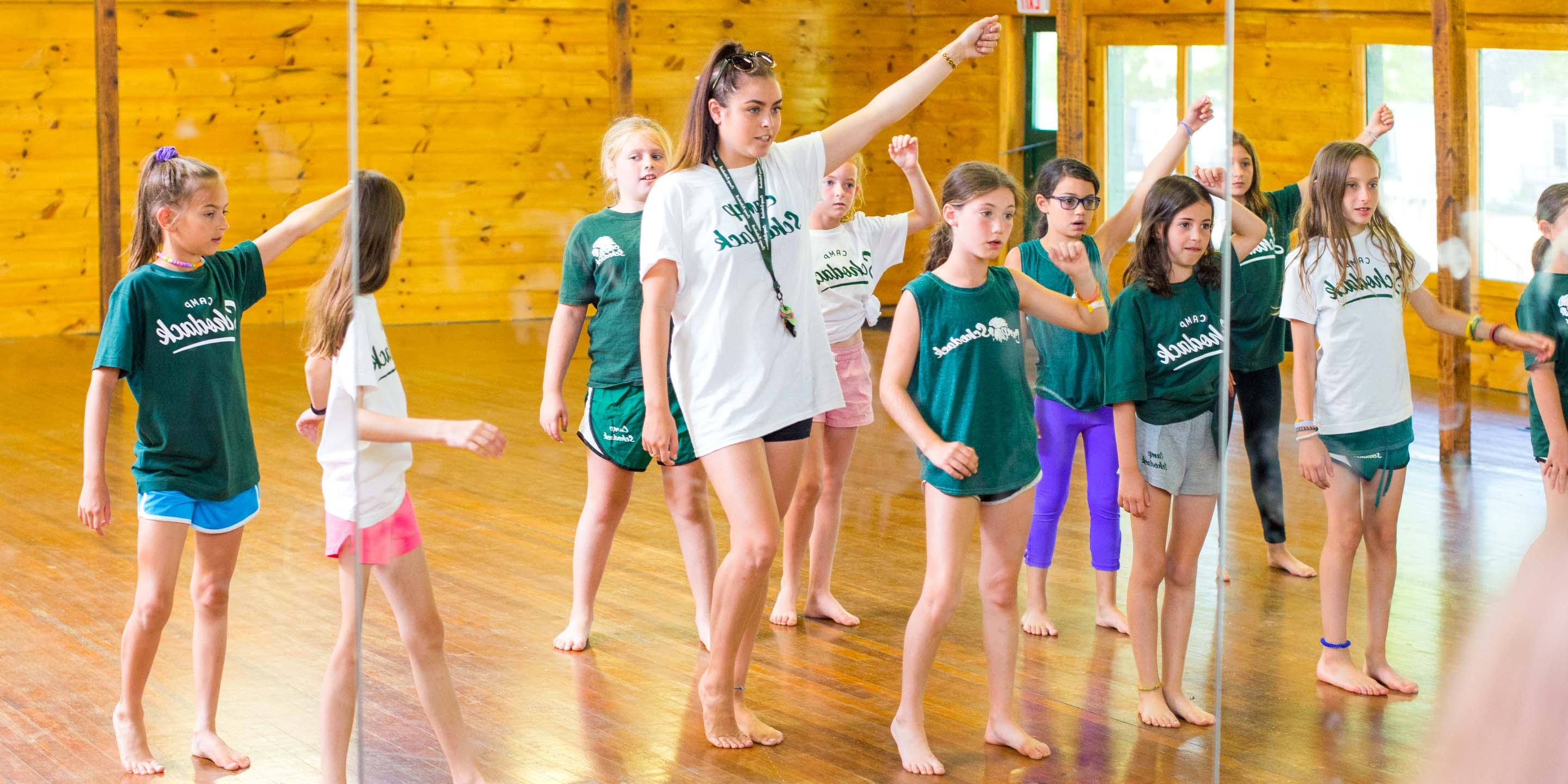 Staff member leads campers in dance practice