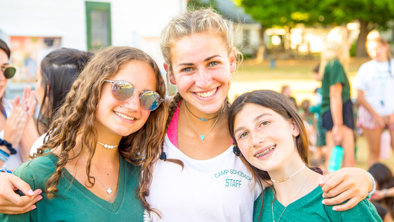 Smiling girls pose with summer camp counselor
