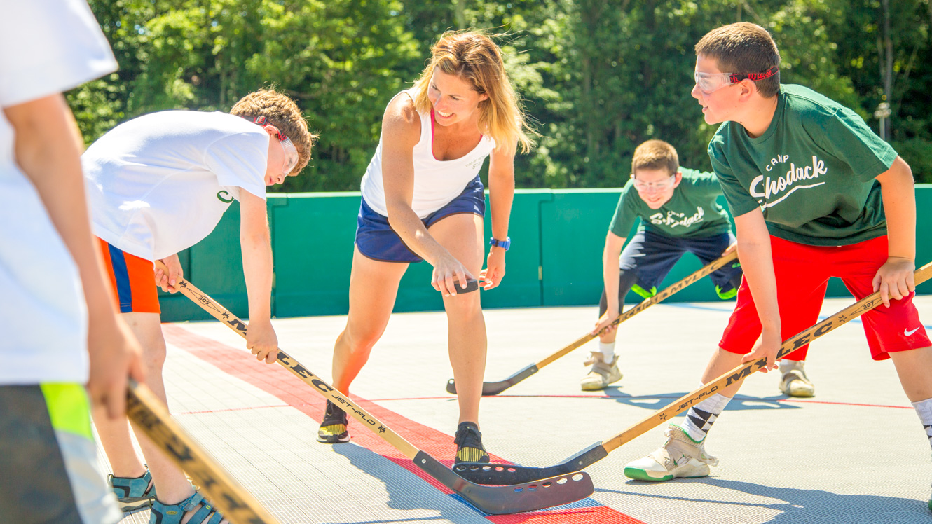 Staff member drops puck for campers playing street hockey