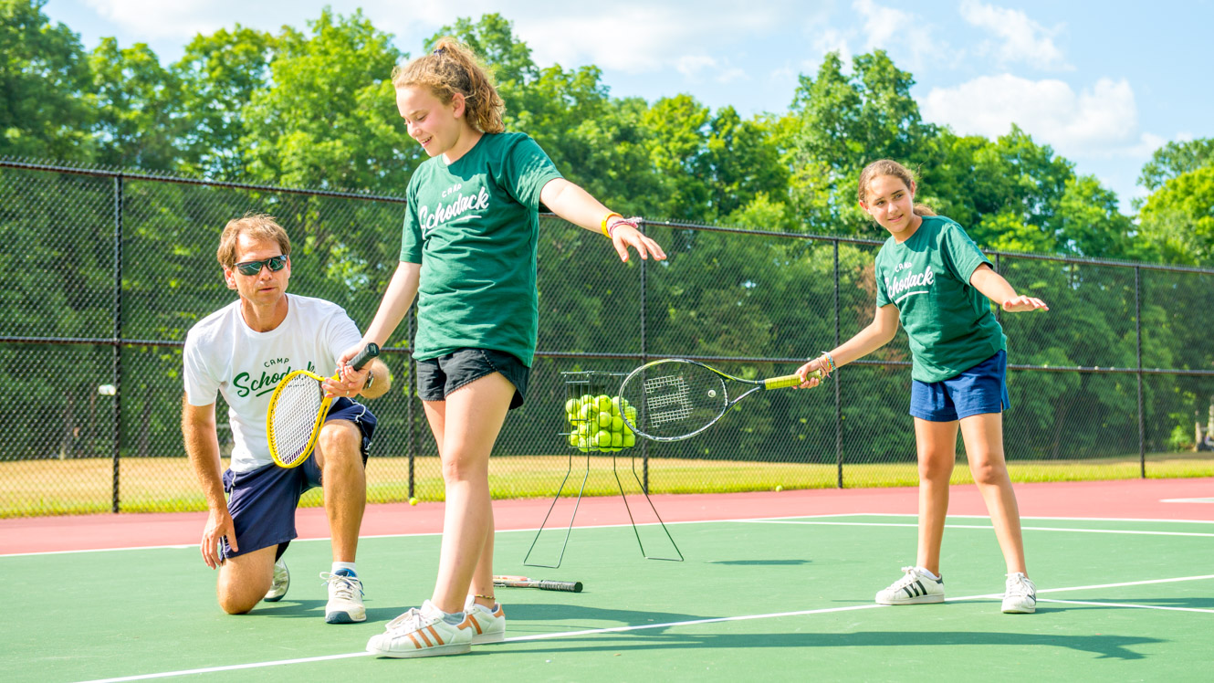 Staff member helps campers with tennis swing
