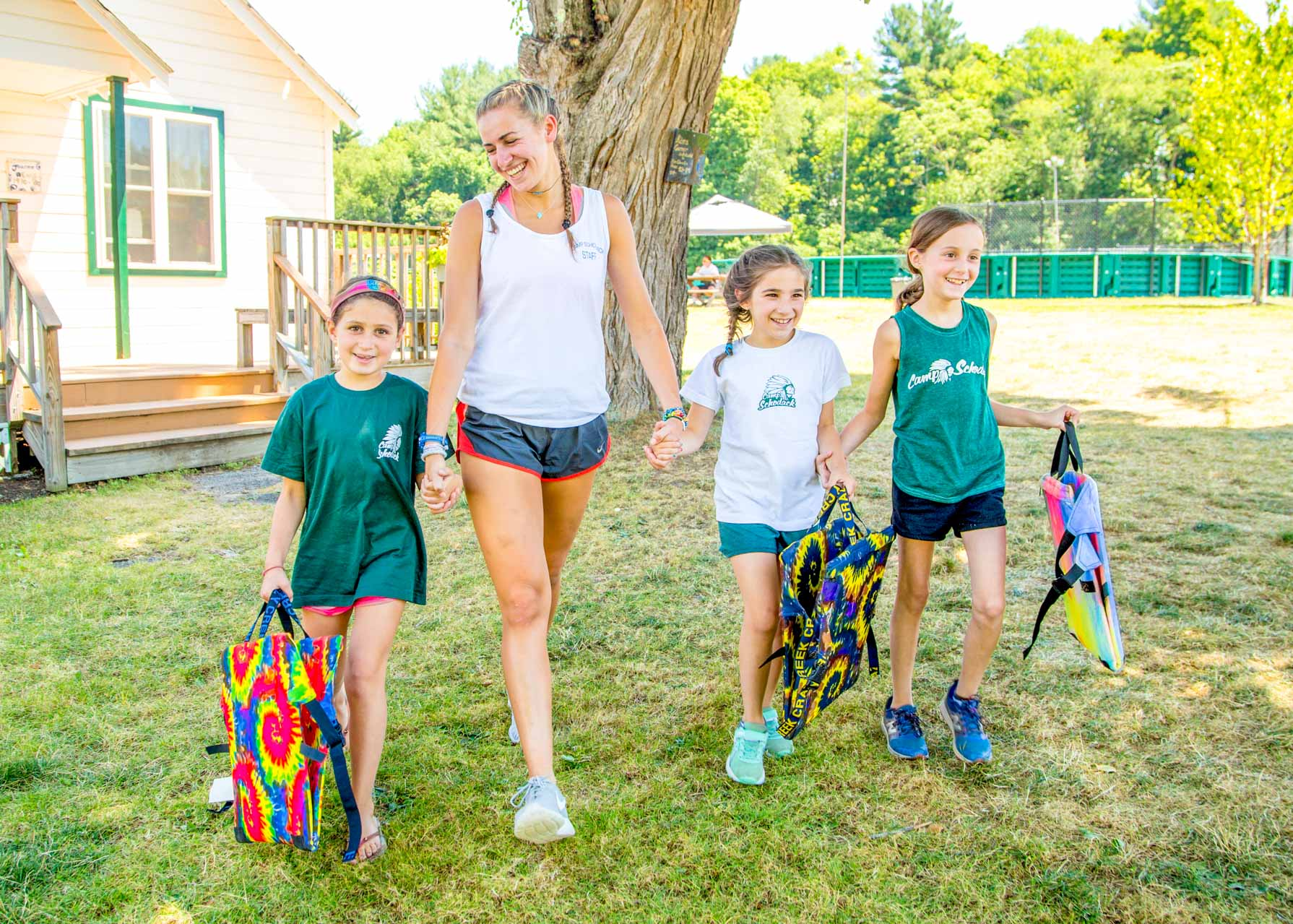 Staff member walks alongside three young campers