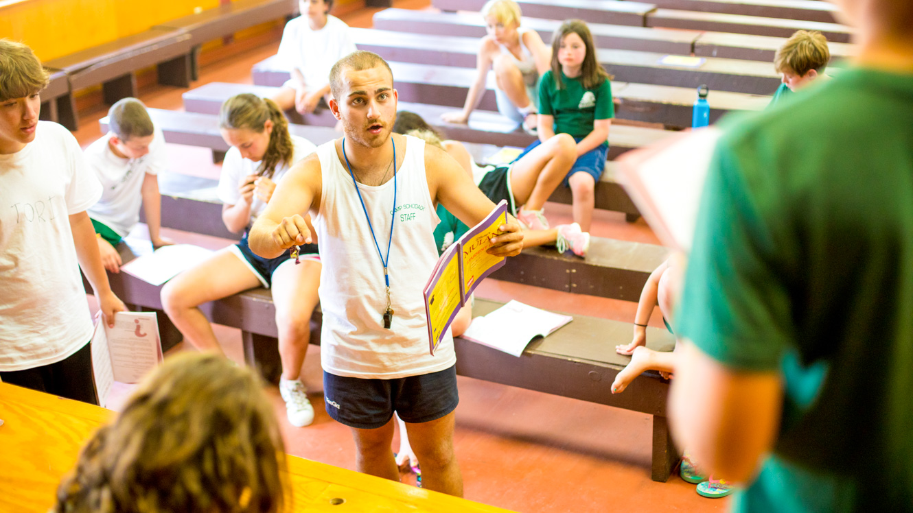 Staff member directs campers rehearsing for play