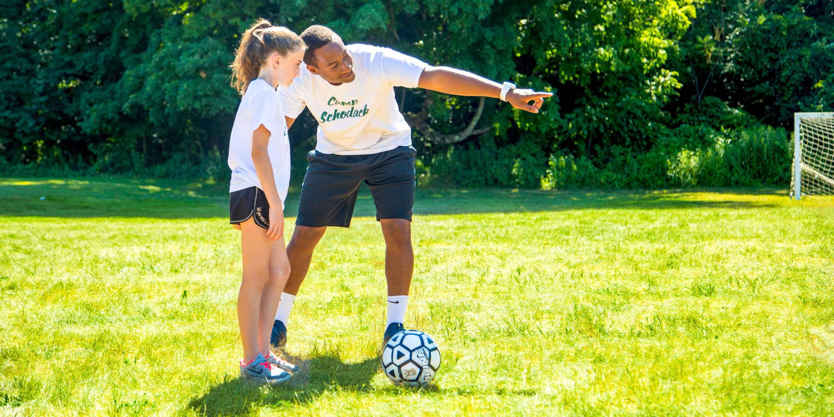 Staff member helps girl practice soccer at summer camp