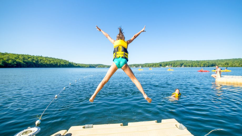 Camper jumps off dock in starfish pose