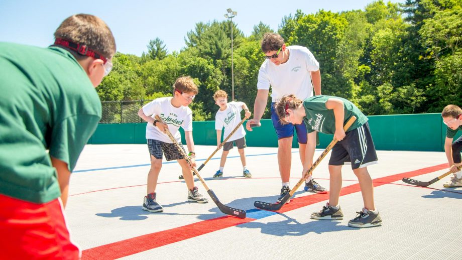 Camp staff member drops puck to begin street hockey game