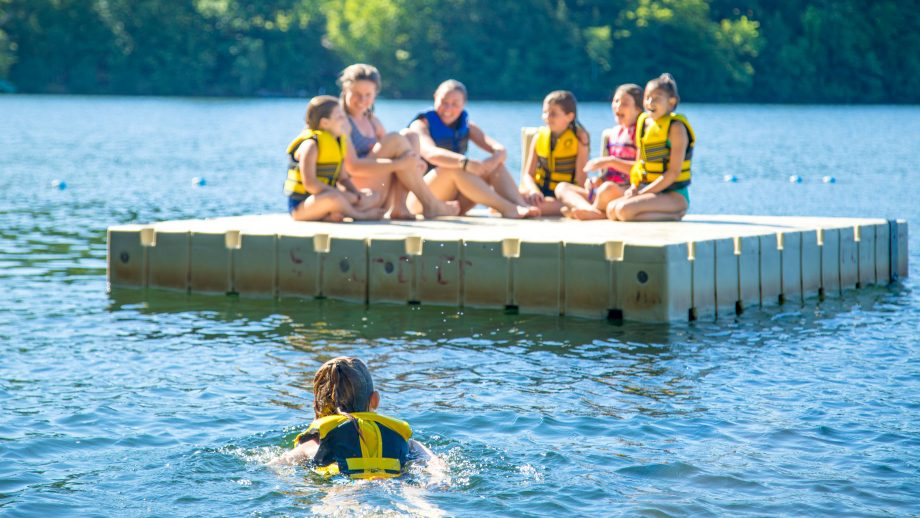 Camper swims out to meet others on floating dock