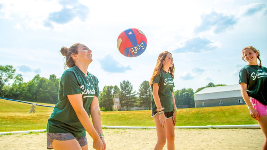 Girl serves volleyball during summer camp game