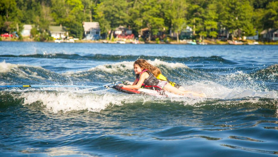 Camper lies on stomach while wakeboarding