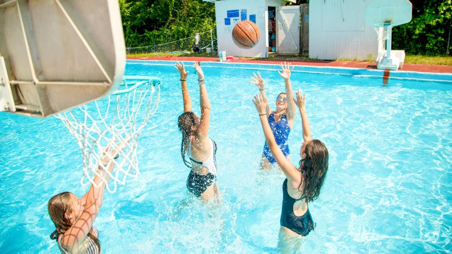 Campers play water basketball in summer camp pool