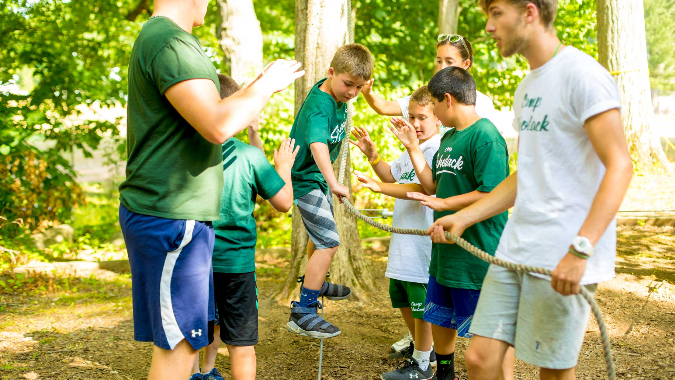 Boys cross low ropes course at summer camp